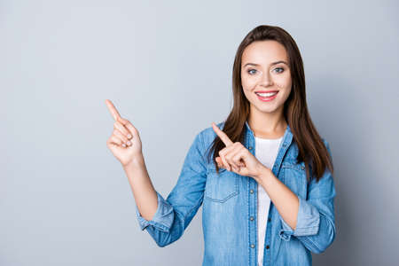 Advertisement concept. Positive, pretty, caucasion woman with beaming smile in jeans shirt  on grey background  is pointing with her two index finger and looking on empty copy space
