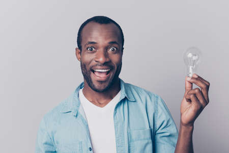 Hooray! Close up portrait of excited cheerful glad delightful handsome shocked amazed astonished man wearing denim jeans shirt holding light bulb isolated on gray background Stok Fotoğraf