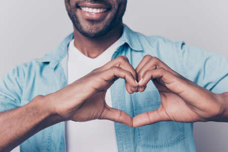 Declaration of love concept! Cropped close up view photo of cheerful loving sincere joyful charming attractive afro gut showing a heart using hands