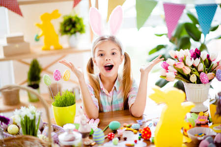 Cute, pretty, impressed, little child with wide open mouth, gesturing with hands, celebrating Easter, wearing bunny ears, costume, sitting at decorated desk