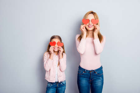 Attractive, nice, cute, sweet, charming daughter and mom, mum standing over gray background, holding four small paper hearts on eyes place, smiling, having fun