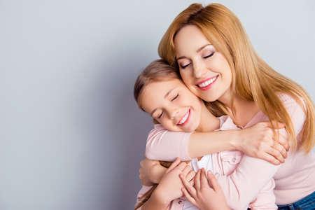 Porträt mit copyspace der hübschen, reizenden Mutter und der Tochter, die über grauem Hintergrund mit nahen Augen, Wochenende, Freizeit, Glück, Spaß, Freizeit, Verwandte umfasst