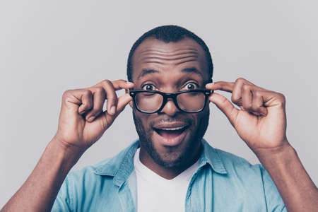 Omg! I can see you perfectly!  I have good vision! Close up portrait of excited cheerful glad satisfied surprised afro guy taking off his unnecessary glasses isolated on gray background
