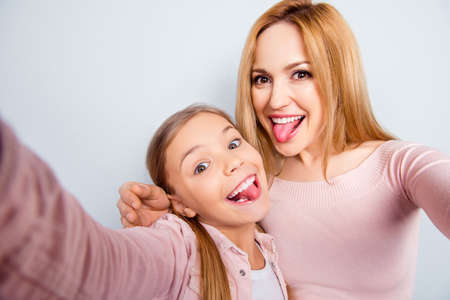 Self portrait of crazy, foolish mother and doughter showing tongue out, kid making selfie on mobile phone over grey background, spending weekend, womans day together