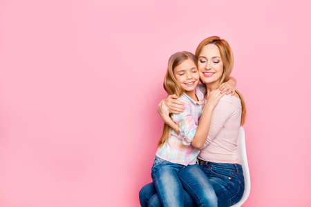 Close up portrait of lovely, charming daughter sitting on mom's hands over pink background, embracing with mum, close eyes, leisure, holidays, weekend, comfort, mother, women's day Stock Photo