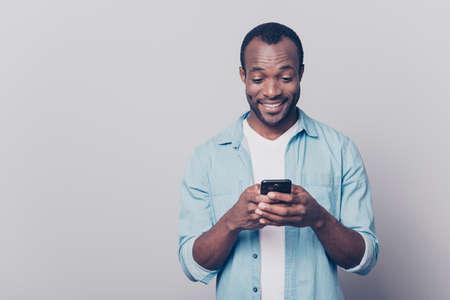 Porträt des hübschen aufgeregten netten frohen herrlichen neugierigen Kerls, der das zufällige Jeansdenimhemd sendet und erhält Mitteilungen zu seinem Liebhaber lokalisiert auf grauem Hintergrund trägt Standard-Bild