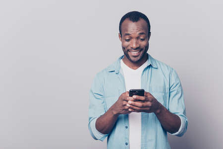 Portrait of handsome excited cheerful joyful delightful curious guy wearing casual jeans denim shirt sending and getting messages to his lover isolated on gray background Standard-Bild