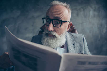 Serious, handsome, astonished, elderly, smart old businessman in glasses and jacket reading newspaper, shocked because of news about politic, bitcoin, finance, economy over gray background
