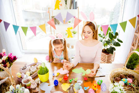 Top view portrait of little, cute, pretty, charming, creative daughter and mommy, drawing, painting easter eggs, wearing bunny ears on head, festive atmosphere at home, preparing for Easter