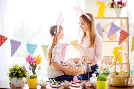 Little daughter sitting on table with colorful decorations, tulips, holding basket with baked cookies, pretty mother standing near here, together wearing bunny ears, looking to each other Фото со стока