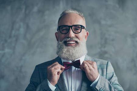 Close-up portret van vrolijke opgewonden met toothy stralende glimlach stijlvolle trendy grijsharige verzorgd scherp gekleed elegante slimme knappe aantrekkelijke ondernemer kiezen strikje geïsoleerd op grijze achtergrond