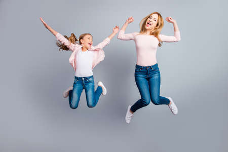 Cute, pretty, playful mother and daughter with open mouth jumping in the air over gray background, celebrating woman's day, yes, done, winners, victory, sisters screaming, shouting Zdjęcie Seryjne - 93601601