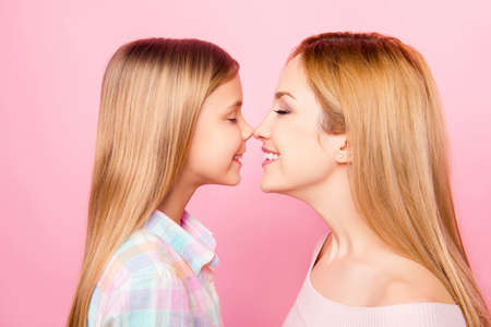 Side view profile of cheerful, nice, cute, dreamy, pretty mother and daughter, rubbing nose to nose with close eyes, pink background, trust, respect, feelings, holiday, weekend, relax