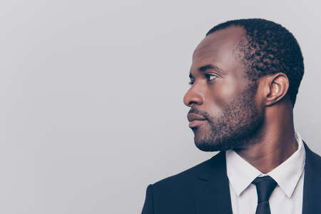 Half-turned side profile close up view portrait of handsome virile masculine attractive confident smart intelligent clever african man looking aside weairng smartsuit isolated on gray background 免版税图像