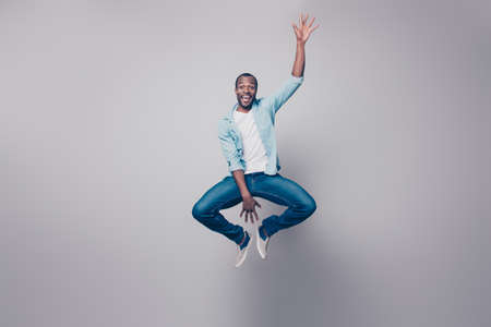 Full-size full-length portrait of cheerful handsome joyful excited delightful impressed surprised afro guy wearing casual denim jeans clothing jumping up, isolated on gray background