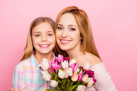 Close up portrait of lovely, charming mummy and daughter with beaming smiles over pink background, having colorful tulips, bonding cheek to cheek, looking at camera, women's day