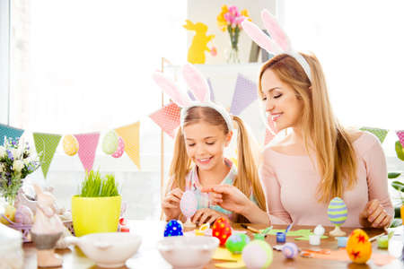 Happy Easter atmosphere! Funny, pretty, creative mom teaching, explain, to her cute, small, joyful daughter how to draw, paint, decorate easter eggs, together wearing bunny ears, sitting at desk Stock Photo
