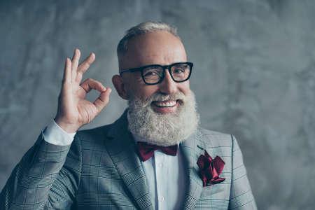 신랑 된 세련 된 콧수염과 쾌활 한 흥분된 초상화를 닫습니다 hipster 할아버지 날카로운 옷을 입고 체크 무늬 자 켓 회색 배경에 고립 된 확인 기호 만들 스톡 콘텐츠
