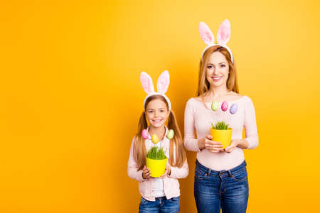 People gatherings family concept. Portrait of childish adorable sweet playful tender gentle mom and preteen girl holding two hand-crafted vases with dotted funny eggs on sticks isolated on background 스톡 콘텐츠