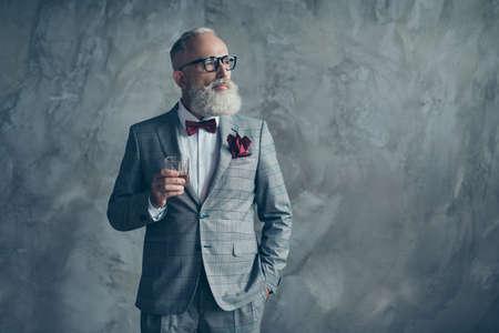 고급스런 라이프 스타일. 자신감이 존경할만한 계획의 초상화 잘 생긴 잔인 한 남성 날카로운 옷을 입고 체크 무늬 회색 턱시도 vinous 손수건 마시는 음