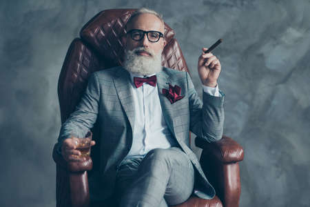 Cool man in glasses, hold cigarette,  glass with brandy, in formal wear, tux with red bowtie and pocket square, sit in leather chair over gray background, looking to the camera, shares, stock, money Foto de archivo