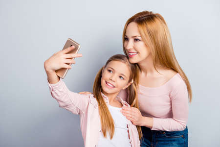 Connection, communication, technology, having video call, sweet kid making selfie on digital, electronic device, smart phone, front camera with her lovely mother over gray background, apps