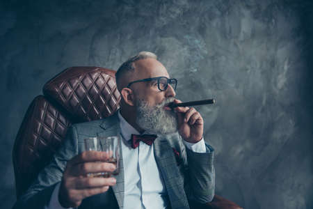 Side profile view of  thoughtful, selective,  investor in glasses, smoke cigar, fume, hold glass with cognac, in tuxedo, suit with red bow, sit in leather armchair over gray background, workplace