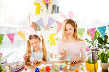Happy Easter atmosphere! Funny, pretty mummy teaching, training her cute, joyful, small daughter draw, paint, handmade decorate easter eggs, together wearing bunny ears Stock Photo