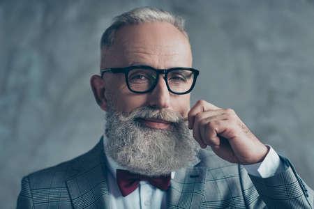 Schließen Sie herauf das Porträt des grinsenden altmodischen modischen eleganten wohlhabenden professionellen flirty Trendsetterhippie-Großvaters, der mit der kastanienbraunen Fliege gekleidet wird, die den weißen Schnurrbart verdreht, der auf grauem Hintergrund lokalisiert wird