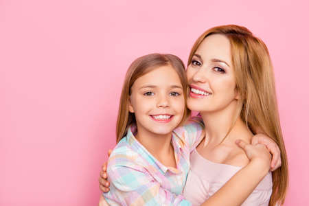 Close up portrait of pretty, charming mother and daughter with beaming smiles over pink background, bonding cheek to cheek, hugging, looking at camera, womens day