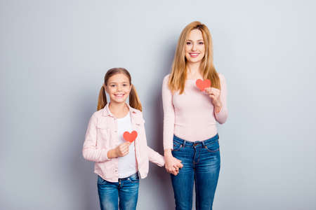 Pretty, nice, cute, charming daughter and mother standing over gray background, holding hands, having, showing two small paper hearts, smiling, looking at camera
