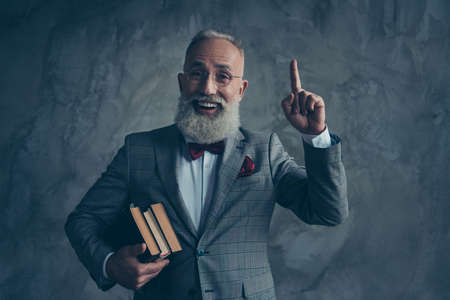 Portrait  of successful, clever attractive, serious millionaire in jacket with bow-tie, in glasses, holding three books in arms, pointing forefinger up, find a great idea over gray background Stockfoto