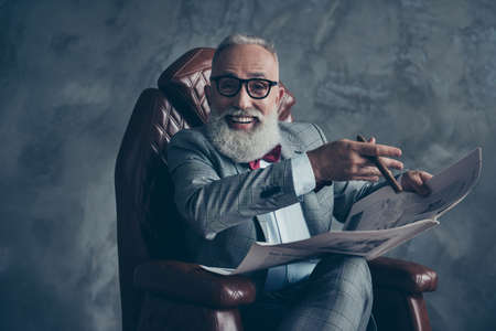 Attractive, rich, old, laughing boss with beaming smile in glasses, tux with red bow, have, hold newspaper, smoke cigarette, sitting in leather armchair in workplace over gray background, relax, fun Фото со стока