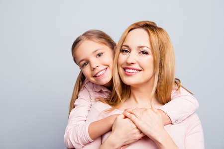 Close up portrait, piggy back style, pretty, cute, nice, charming woman and daughter, kid embracing her mom from back, together smiling, looking at camera over gray background