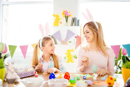 Funny, cheerful, joyful mum teaching, training her cute, pretty, small, little daughter draw, paint, decorate easter eggs, together wearing bunny ears, looking to each other, preparing for Easter