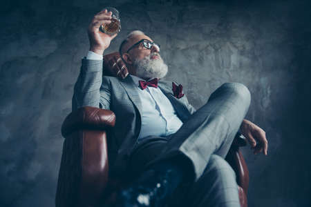 Bottom view of attractive, old investor in spectacles, hold glass with brandy, in tuxedo with red bow tie and pocket square, sit in leather chair over gray background, looking at the side