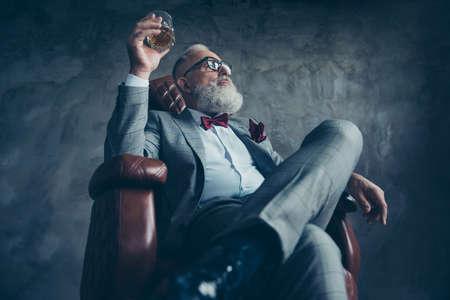 Widok z dołu atrakcyjnego, starego inwestora w okulary, trzymaj szkło z brandy, w smokingu z czerwoną muszką i kieszonką, usiądź w skórzanym fotelu na szarym tle, patrząc z boku
