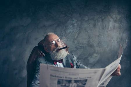 Portret van brute aantrekkelijke oude man in smoking bedrijf, kijkend naar de krant, het lezen van nieuws over financiën, politiek, economie, rokende sigaar, zittend in een leunstoel, grijze achtergrond