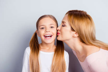 People growing-up generation close beloved relatives concept. Close up portrait of delightful impressed cute lovely girl receives gets kiss in cheek from blonde pretty mum isolated on gray background