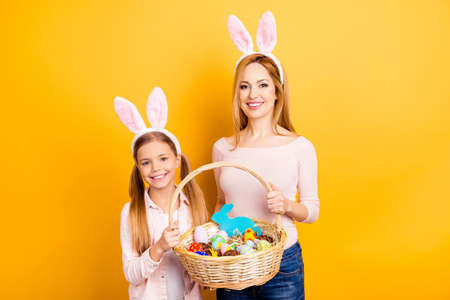 Portrait of adorable cute gentle beautiful sensible careless dreamy family holding together one whisker basket with handmade painted chocolate eggs isolated on bright yellow background