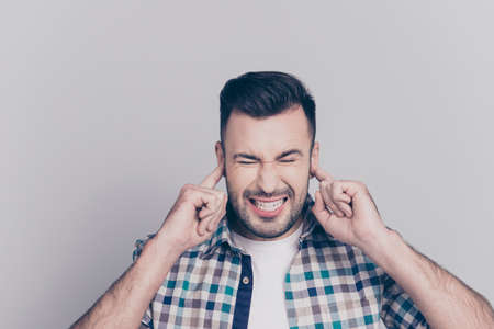 Stop talking! Portrait of tired young guy, closing his eyes and ears with fingers, clench teeth, standing over grey background Stock Photo