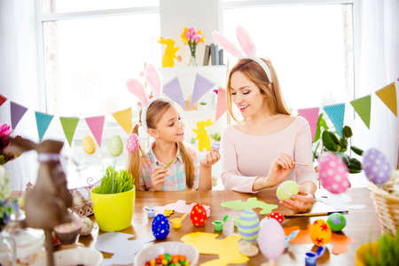 Happy Easter atmosphere! Cute, little, joyful daughter show to creative, funny, pretty, excited mommy her painted, decorated easter eggs, together wearing rabbit costume