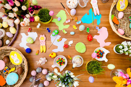 Top view of easter composition with chocolate, colored eggs, papper rabits, gingerbread, flowers, dragee, tassel, paints on wooden background 版權商用圖片
