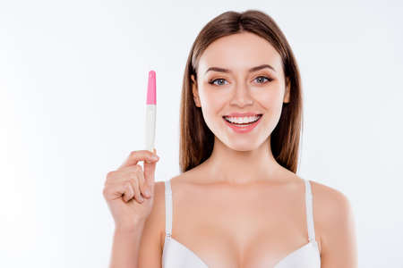 Wow I am pregnant! Close up portrait of attractive beautiful cute tender lovely amazed astonished woman demonstrating positive result on pink and white test stick isolated on background copy-space