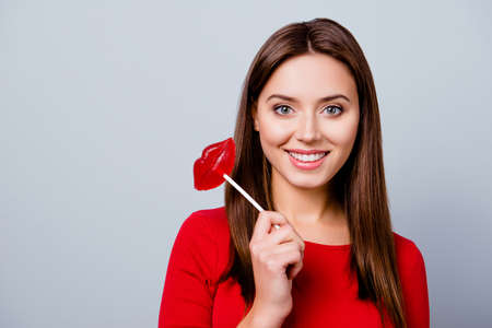 Charming, pretty, cute, lovely girl over gray background holding candy in lips shape on stick, looking at camera, in casual outfit
