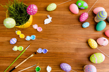 Top view portrait with copy space for text of easter objects on wooden brown background laying colored eggs on sticks, flower, paints and tassels