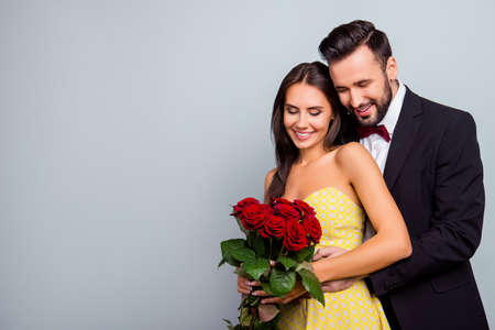 Portrait photo with copy space of charming, lovely, cute couple in formal wear, dress hugging and looking at  bouquet of red roses, wife and husband celebrating  14 february on grey background