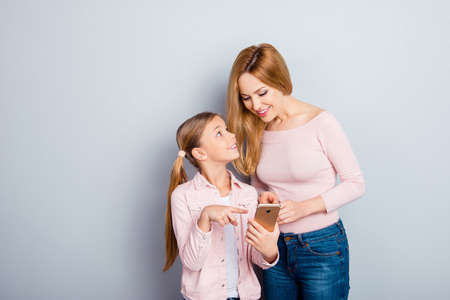 Attractive, nice, cute kid indicate with index finger on digital smart phone screen to her lovely mother, showing something interesting, together doing online shopping