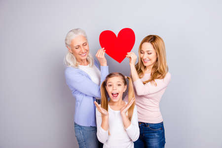 Emotional feeling tenderness gentle warmth concept, Beautiful mum and delightful granny are holding big bright red heart over joy joyful cheerful small girls head isolated on gray background