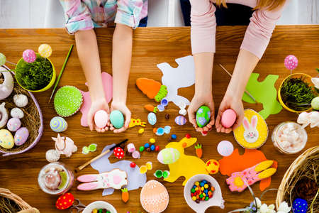 Top view horizontal portrait of attractive, beautiful, colorful handmade easter objects, subjects, things, baked cookies laying on wooden table and hands showing painted, decorated small, little eggs Stock Photo